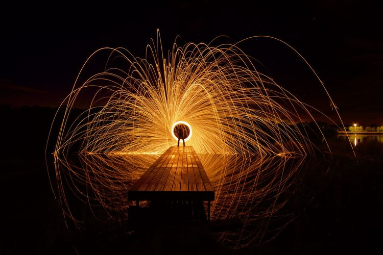 Person spinning wire wool on pier