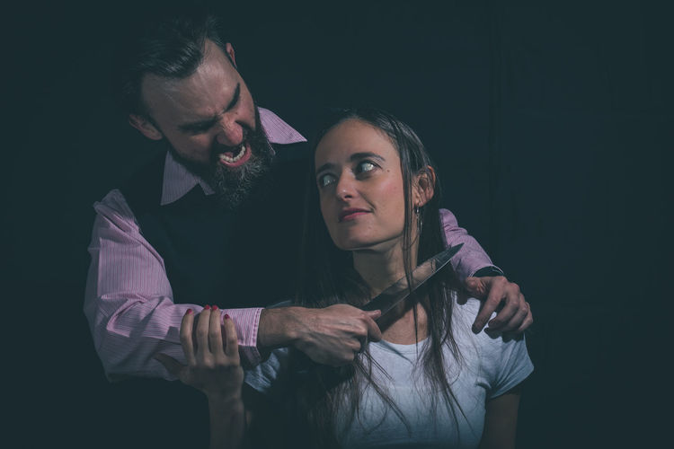 Angry Man Shouting While Holding Knife By Woman Against Black Background