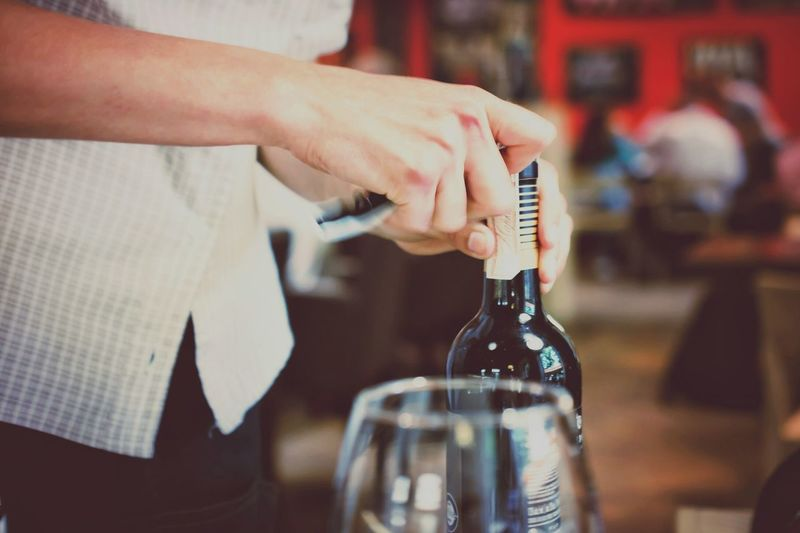 Midsection of man opening wine bottle