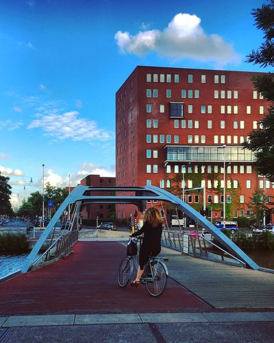City View  City Life Bridge Structure Bicycle Woman Building Red End Of The Day Sunny Day Blue Sky Streetphotography Light And Shadow Architecture River Canal Amstel Amsterdam Netherlands Mmaff From My Point Of View Eye4photography  EyeEm Gallery Taking Photos Hello World