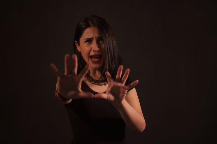 Scared Woman Gesturing While Standing Against Black Background