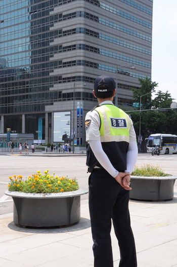 Rear view of police man standing on street