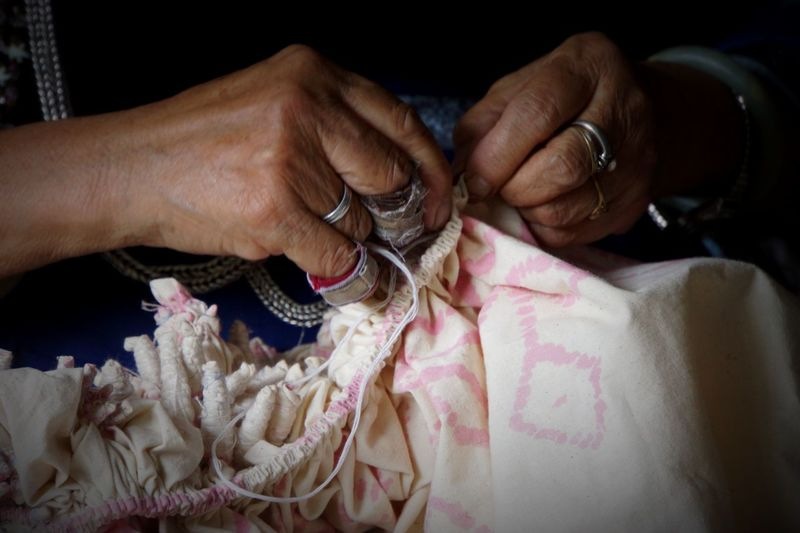 Midsection of woman sewing fabric