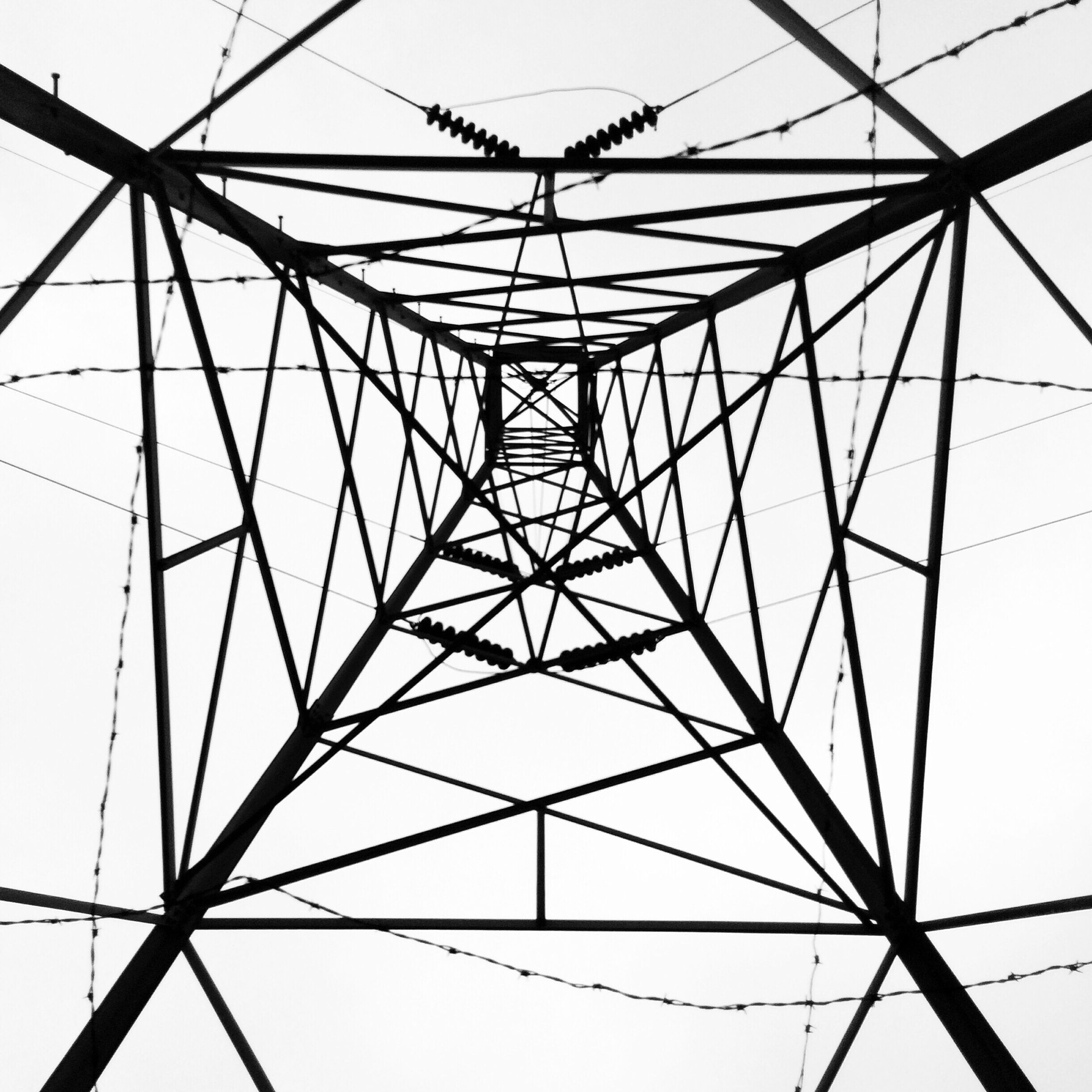 low angle view, power line, electricity pylon, power supply, fuel and power generation, electricity, connection, clear sky, cable, technology, complexity, built structure, sky, directly below, architecture, day, backgrounds, no people, outdoors, full frame