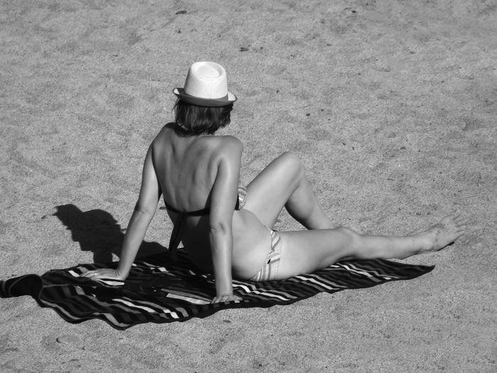 High Angle View Of Woman In Bikini Sunbathing At Beach On Sunny Day