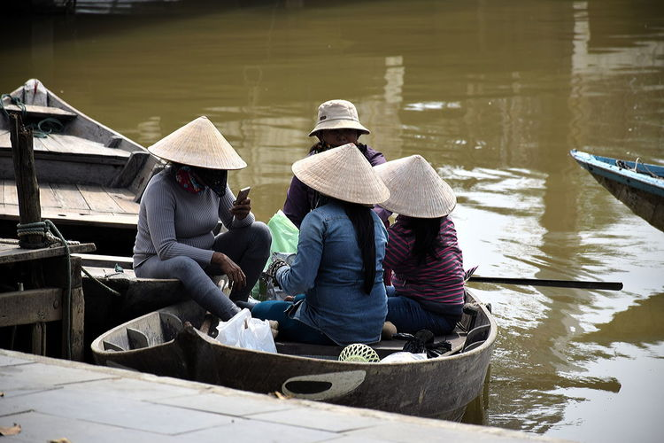 Four Vietnamese inhabitants of Hoi An sitting in a traditional boat - with modern Smartphone Adult Adults Only Boat In Vietnam Boat With Four People In Harbor Day Hat Hoi An, Vietnam Men Occupation Only Men Outdoors People Traditional Vietnamese With Smartphone Vietnam Vietnamese People In Boat Water Working