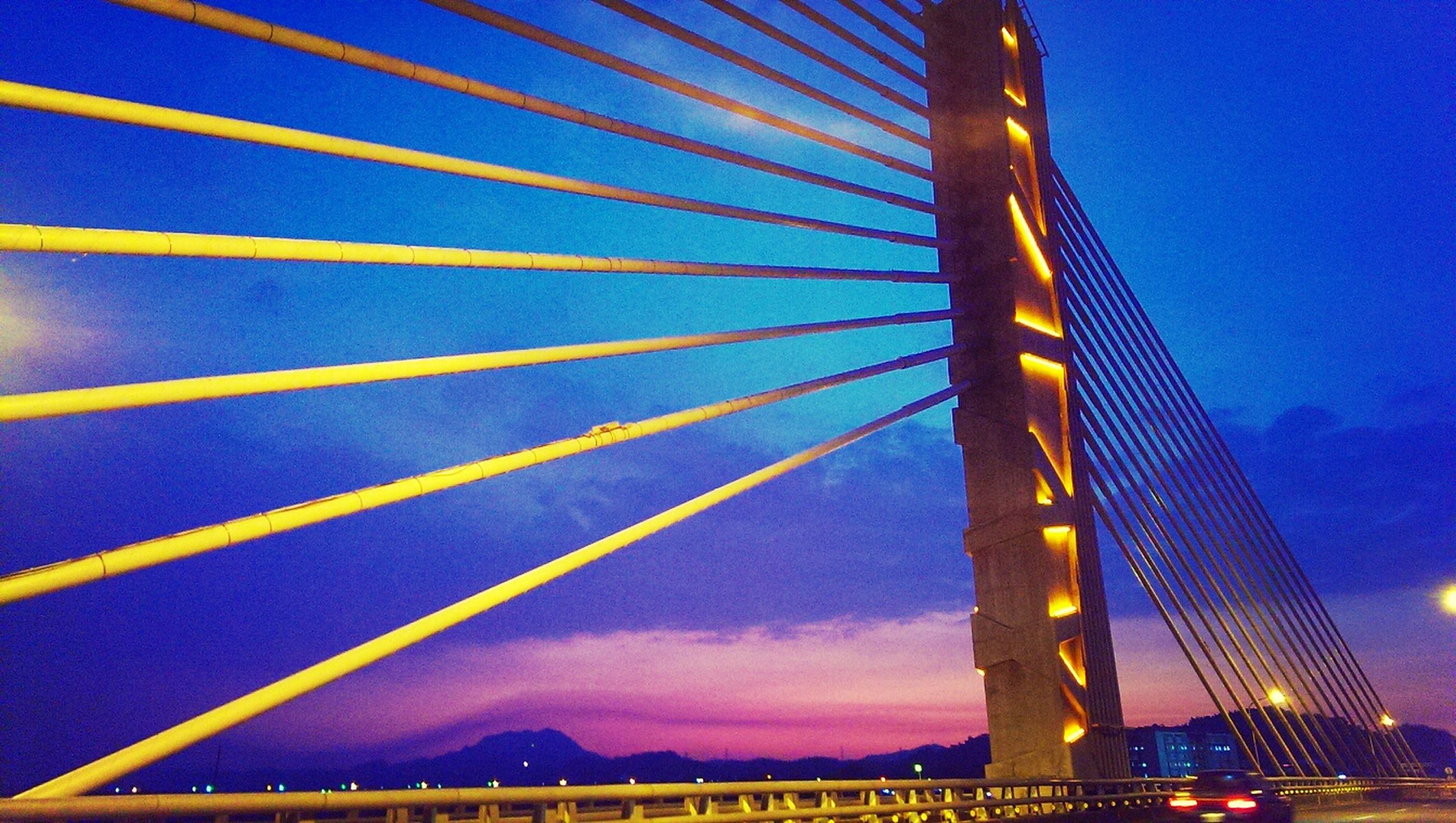 built structure, architecture, blue, illuminated, connection, sky, bridge - man made structure, suspension bridge, city, sunset, dusk, low angle view, building exterior, engineering, travel destinations, transportation, famous place, long exposure, clear sky, outdoors