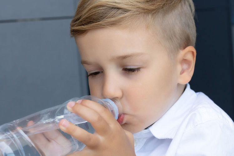 Portrait of boy drinking water from glass