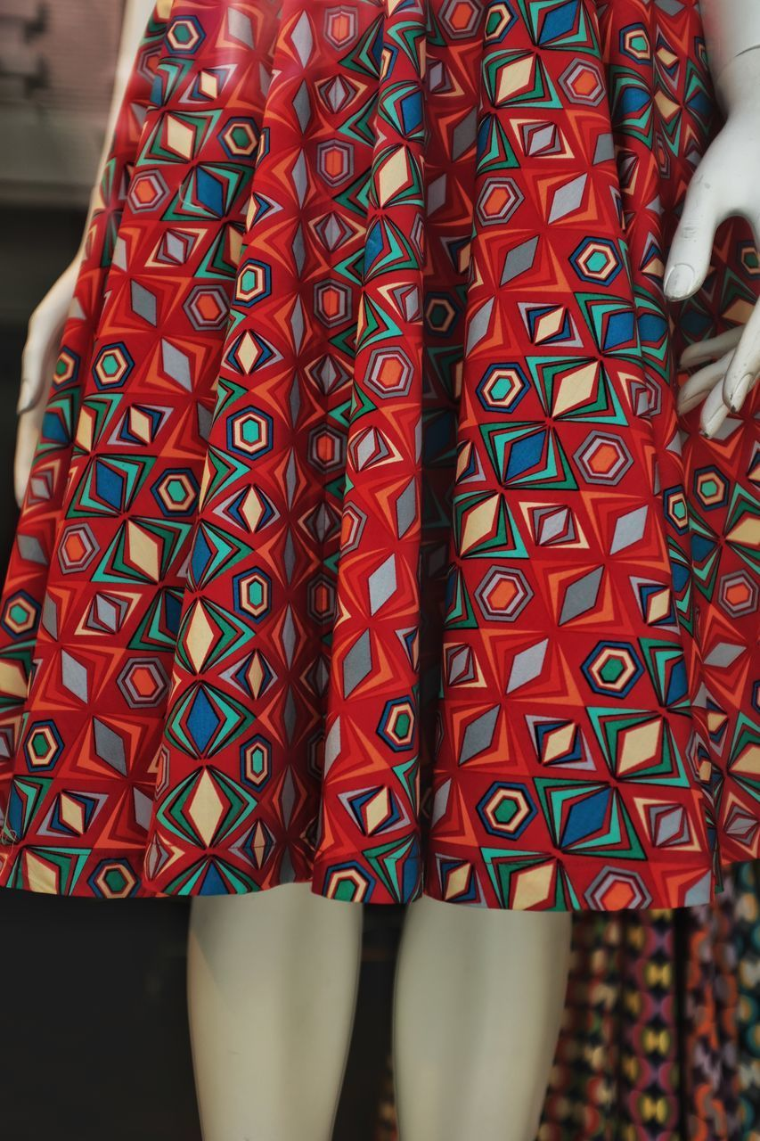 LOW SECTION OF WOMAN STANDING ON MULTI COLORED PATTERN