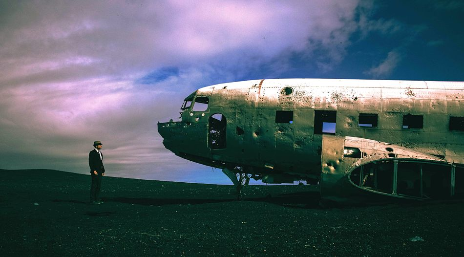 Full Length Man Looking At Damaged Airplane Against Cloudy Sky