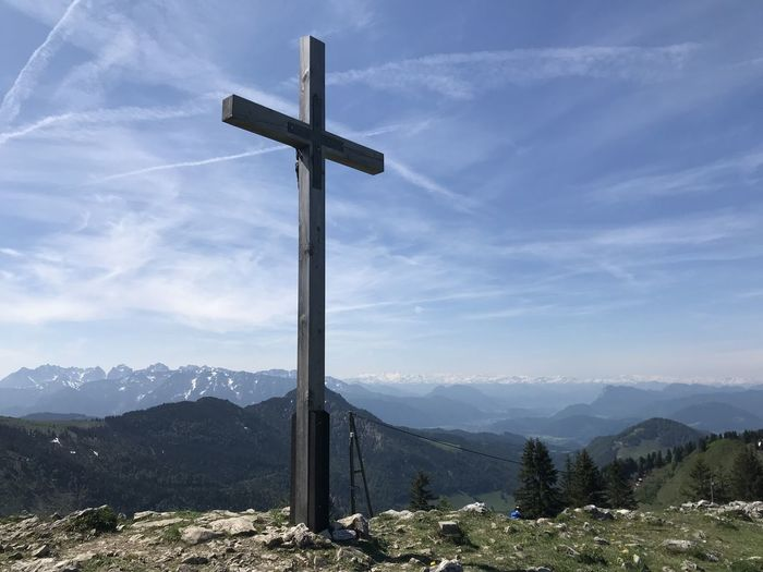 Cross on mountains against sky
