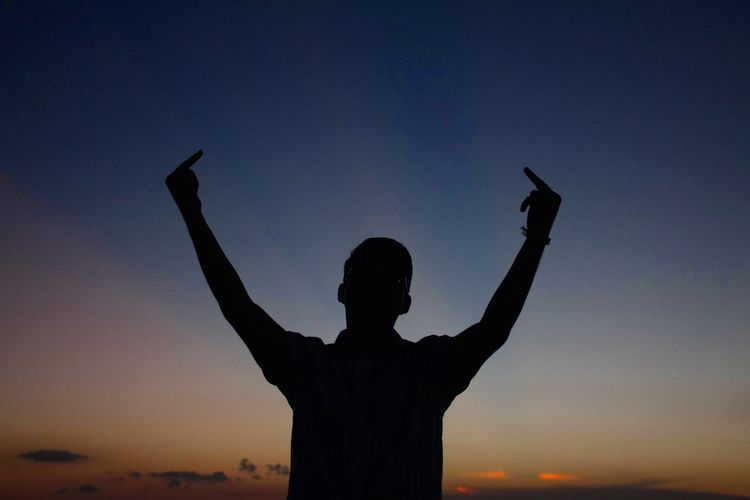 Silhouette man showing middle fingers while standing against sky during sunset