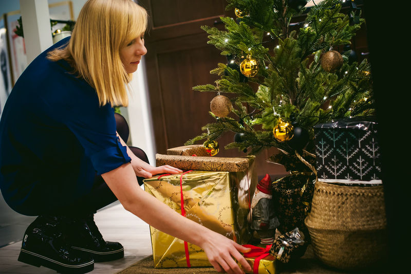 Side view of young woman arranging gift by christmas tree at home