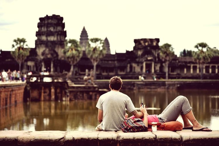 Angkor Wat Cambodia Sitting Water History Adult Built Structure Architecture Travel Destinations Two People Vacations Old Ruin People Building Exterior Adults Only Outdoors Sky Togetherness Travel Lake Relaxation Young Adult Love Sweet♡