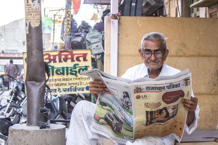 Portrait of man sitting in city