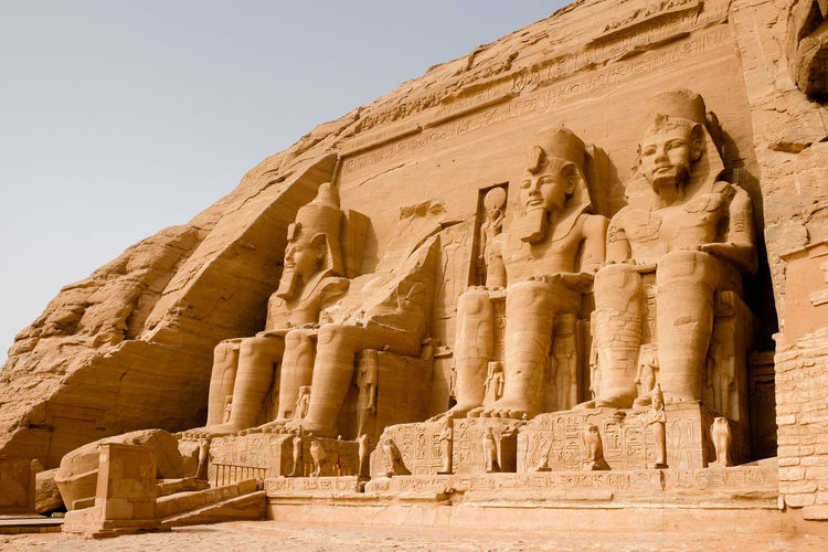 Huge statues of egyptian king ramses ii seated at the entrance to the great temple at abu simbel