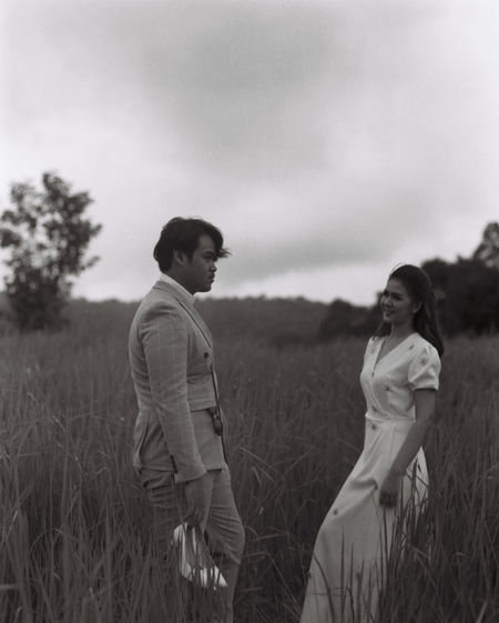 Young couple on field against sky