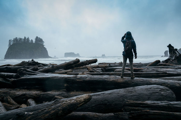 Rear view of woman standing on log against sky