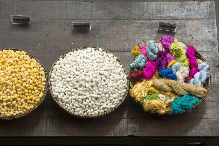 High angle view of multi colored silk cocoons in wicker basket at table