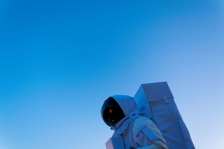 Low angle view of person in astronaut costume against clear blue sky