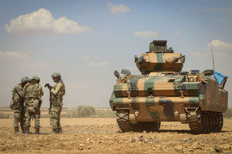 Soldiers discussing while standing by armor tank against sky