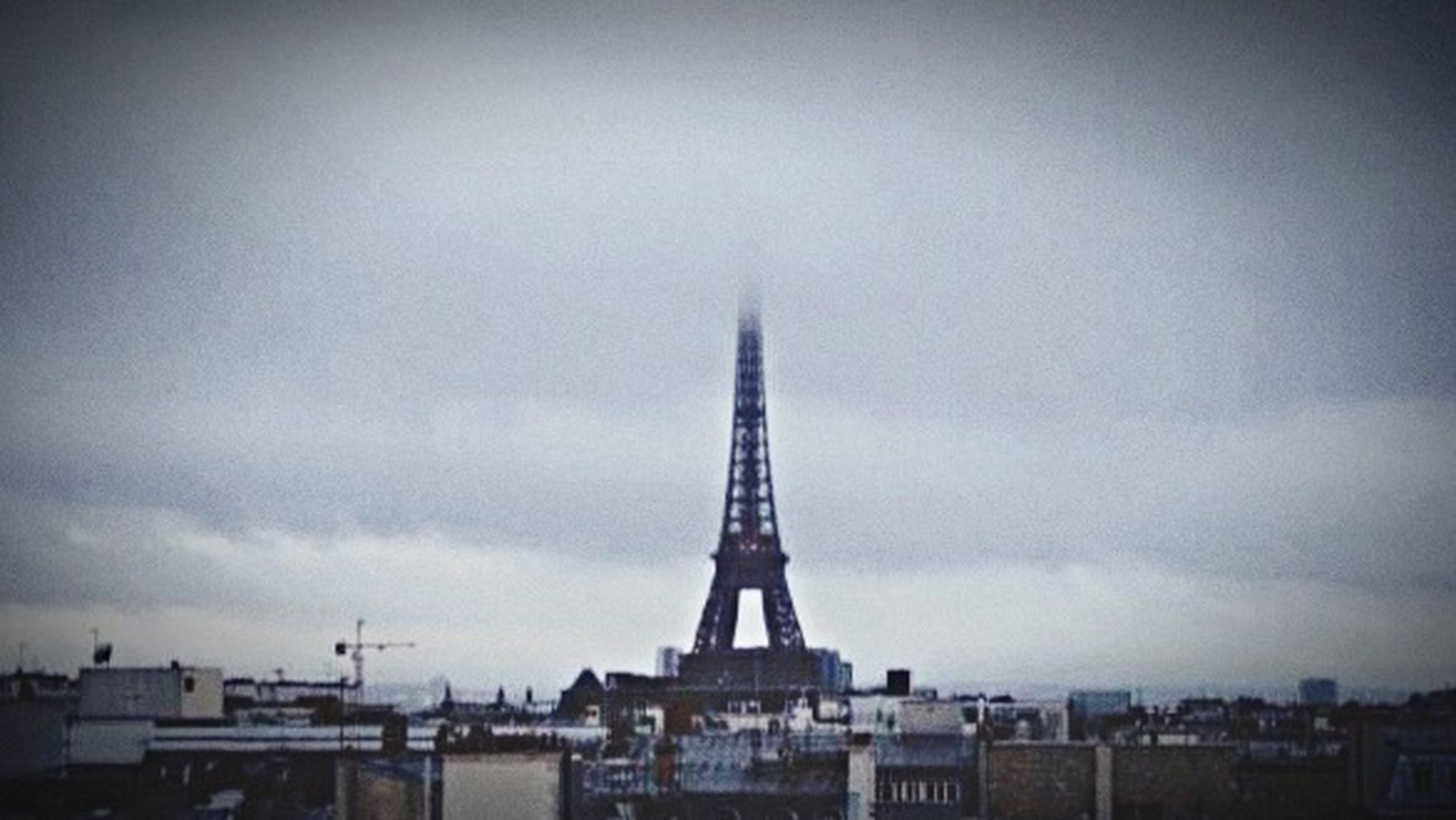 architecture, built structure, sky, low angle view, cloud - sky, building exterior, cloudy, eiffel tower, tower, tall - high, city, overcast, international landmark, weather, travel destinations, famous place, capital cities, dusk, cloud, outdoors
