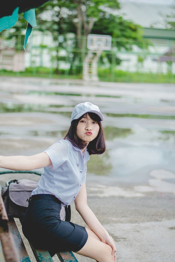 pretty girl collegian Cap Casual Clothing Contemplation Day Focus On Foreground Front View Leisure Activity Lifestyles Looking At Camera Nature One Person Outdoors Portrait Real People Sitting Three Quarter Length Water Young Adult