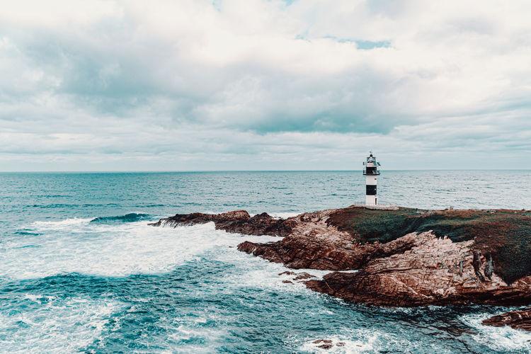 Lighthouse on rocks by sea against sky