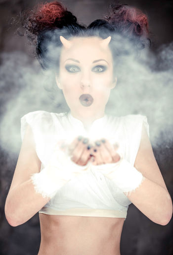 Digital Composite Image Of Horned Woman Blowing Powder