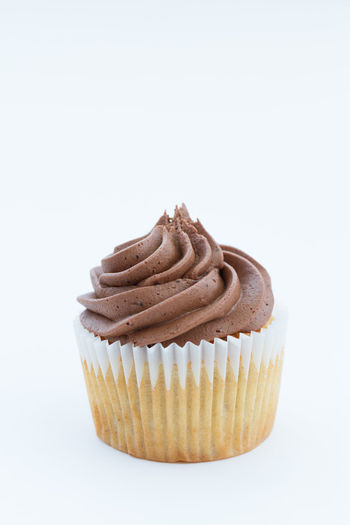 A chocolate cupcake with swirled, chocolate frosting or icing on an isolated white background. Portrait orientation. Bake Bakery Baking Bun Buns Cakes Chocolate Chocolate♡ Cupcake Cupcakes Diet Frosting Iced Icing Indulgence Overindulgence Sugar Sugary Sweet Sweet Food Swirl Treat Unhealthy Eating Unhealthyfood White Background