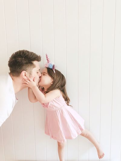 Father Kissing Daughter Against White Wall