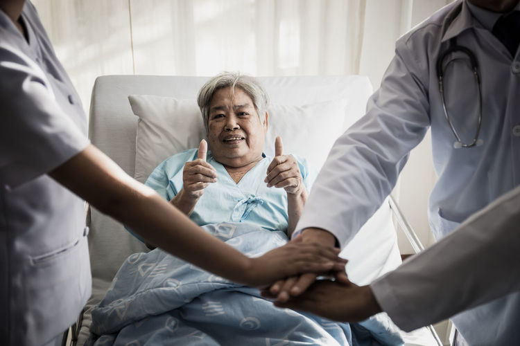 Portrait of female senior patient showing thumbs up signs by doctors stacking hands