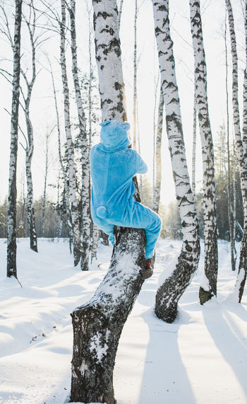 Rear View Of Mid Adult Man Climbing Tree In Forest During Winter