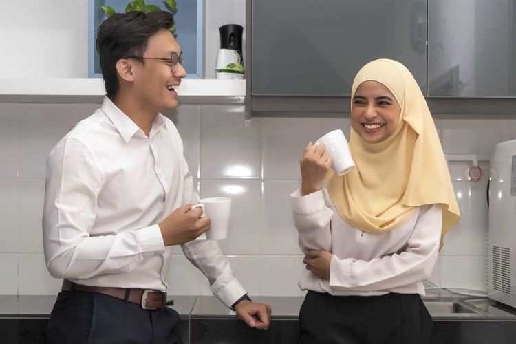 Two young executive malay having a break at pantry Young Adult Two People Standing Young Men Smiling Front View Young Women Three Quarter Length Real People Men Lifestyles Adult People Clothing Happiness Waist Up Teeth Togetherness Males  Toothy Smile