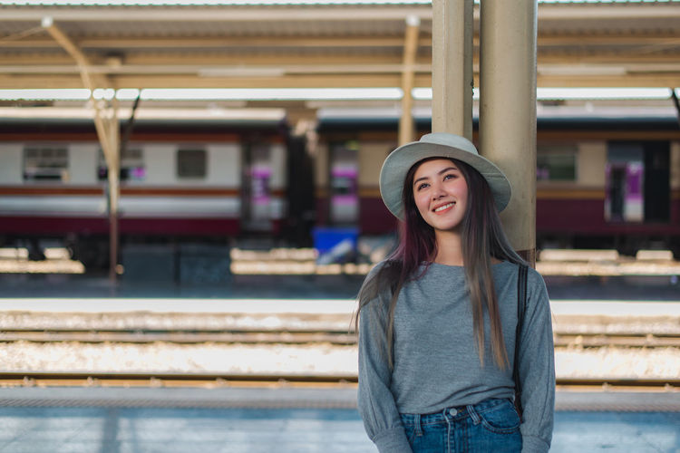 Hat One Person Standing Portrait Casual Clothing Real People Young Adult Leisure Activity Architecture Front View Clothing Smiling Focus On Foreground Rail Transportation Lifestyles Young Women Looking At Camera Happiness Beautiful Woman Hairstyle Hair Outdoors Train Train Station Waiting Happiness Happy Standing Railroad