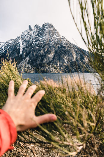 Cropped hand of person gesturing towards mountain against sky