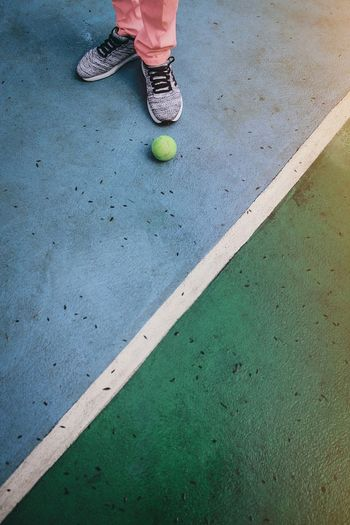 Low section of person playing with ball on floor