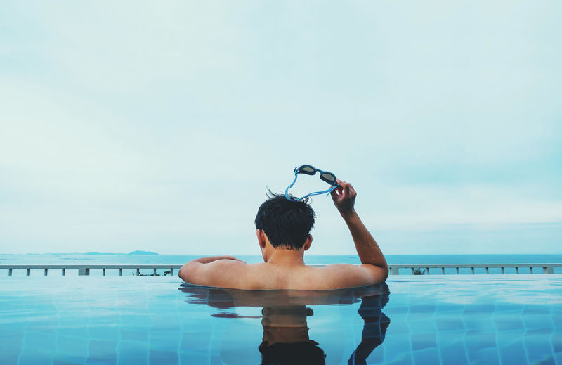 Rear view of shirtless man holding swimming goggles in swimming pool against sky