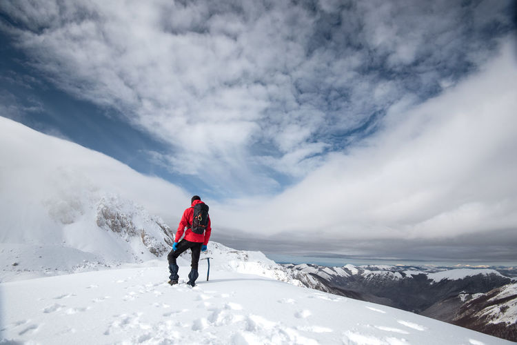 Rear view of man walking on snowcapped mountain against sky