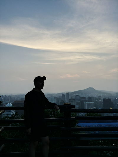 Silhouette man standing by railing against sky during sunset