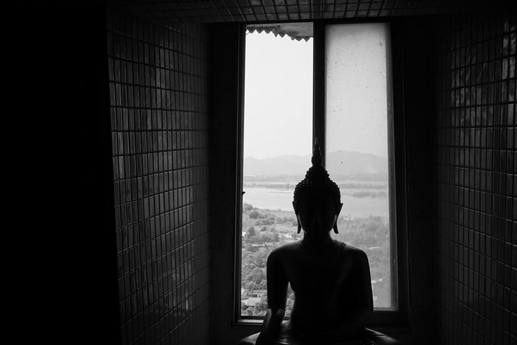 Scenic view of silhouette statue of the meditating buddha next to window