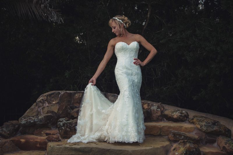 Bride with hand on hip wearing wedding dress while standing on rock
