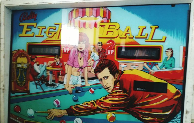 "Top Section of Pinball machine """" EIGHT BALL """" Vintage 1970's Popular Pinball Machine Game EIGHT BALL Pinball Machine Top Section Multi Colored Painted Image Close-up"