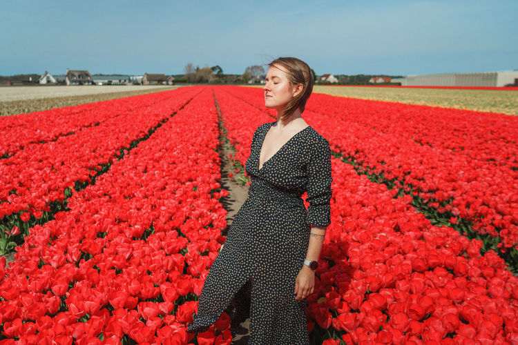 Woman standing on tulip field