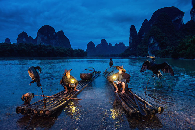 Men With Illuminated Lanterns Sitting On Wooden Raft In Lake