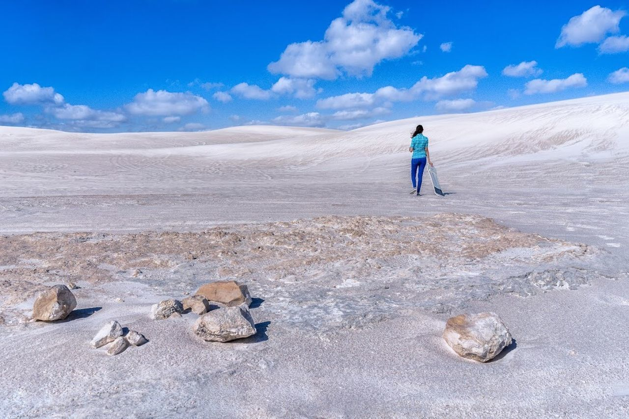 sky, land, full length, one person, cloud - sky, nature, environment, day, landscape, cold temperature, leisure activity, scenics - nature, beach, water, snow, blue, mineral, adult, salt flat, outdoors