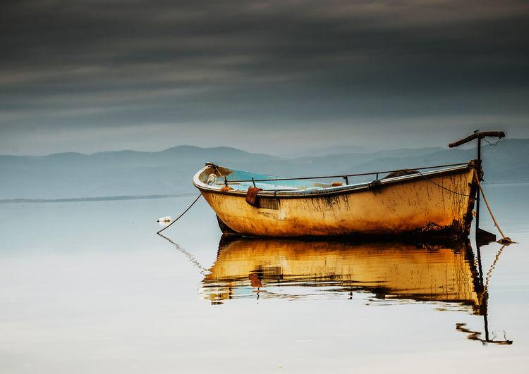 Abandoned ship moored on sea against sky