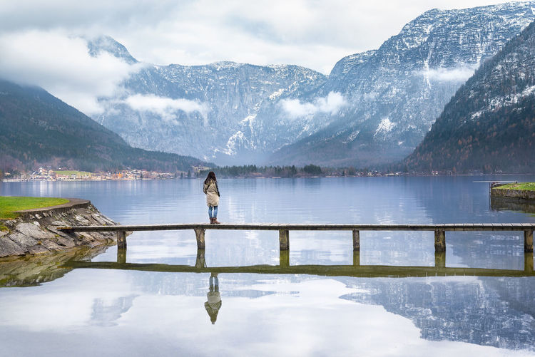 Woman Standing On Bridge Over Lake Against Mountains
