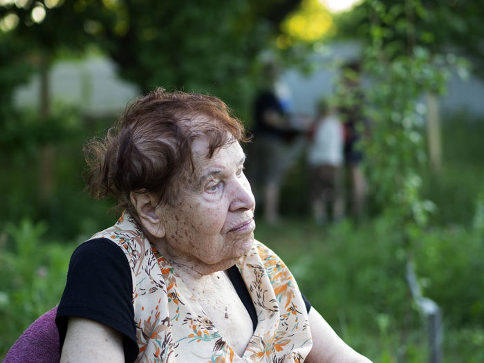 Thoughtful Senior Woman Looking Away While Sitting In Back Yard