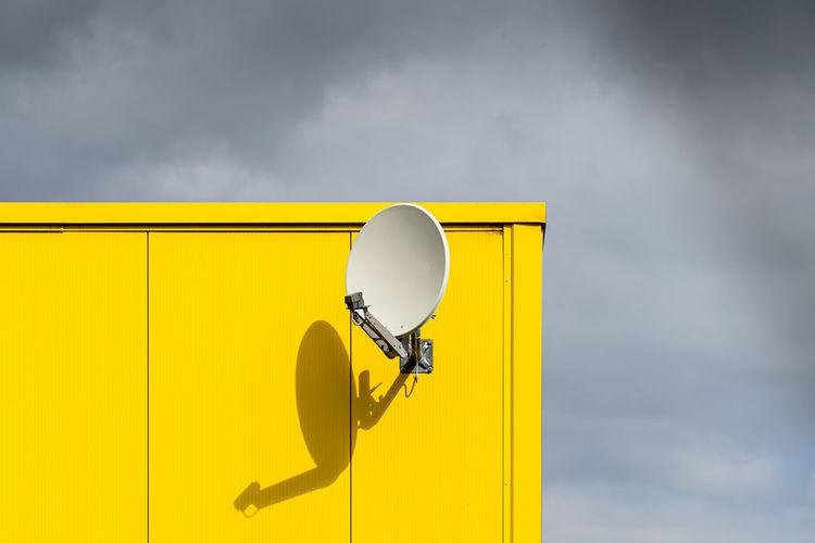 Satellite dish against yellow wall